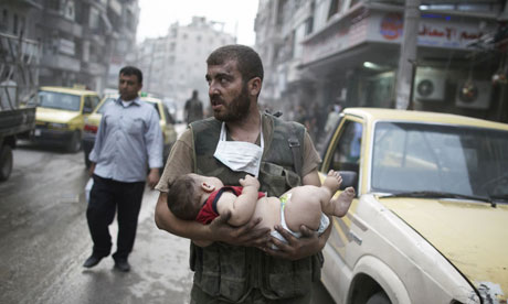 A Free Syrian Army fighter carries a baby, the only survivor in his family after an artillery round destroyed his home in Aleppo this month. Photograph: Sipa USA/Rex Features