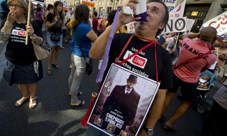 A government employee holds a poster depicting Spain's prime minister Mariano Rajoy as a public enemies, at a demonstration against the government's latest austerity measures. Photograph: Pierre-Philippe Marcou/AFP/Getty Images