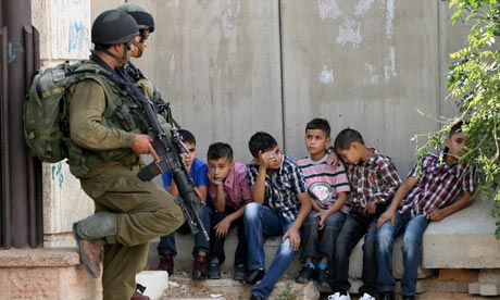 Israeli soldiers stand guard over Palestinian children arrested in the West Bank city of Hebron.  Photograph: Abed Al Hashlamoun/EPA